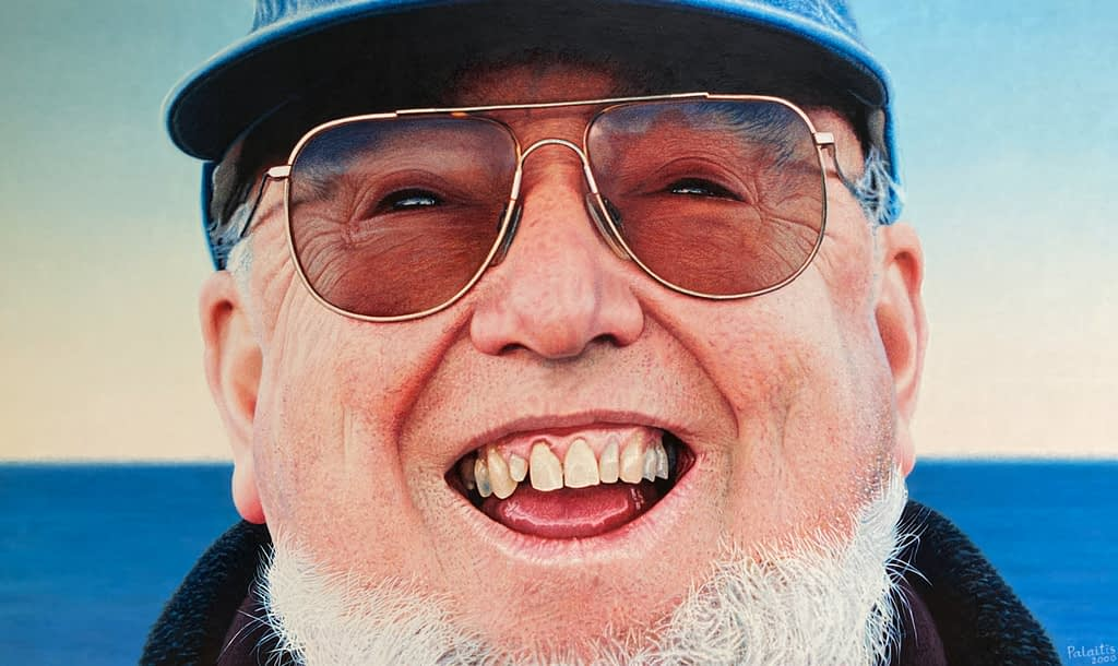 Oil painting by Josonia Palaitis depicting a close up view of the face of Thomas Keneally smiling with his teeth showing wearing sunglasses and a blue cap with the ocean horizon in the background