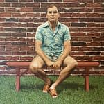 Oil painting by Josonia Palaitis depicting politician John Howard sitting on a bench in front of a brick wall wearing sandals, shorts and a short-sleeved paisley blue shirt