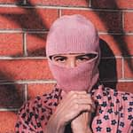 Self portrait painting by Josonia Palaitis depicting the artist wearing a pink balaclava and standing in front of a brick wall