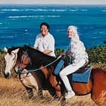 An oil painting by Josonia Palaitis depicting a couple on horseback in fron to a big blue ocean