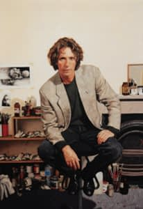 Portrait painting by Josonia Palaitis depicting cartoonist Bill Leak sitting on a stool in his studio with brushes and paints in the background