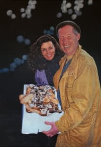 Oil painting by Josonia Palaitis depicting two friends after a day picking mushrooms with the man holding a white box full of mushrooms and the woman beside him, both smiling triumphantly as darkness sets in and the hint of a flash photograph is discerned