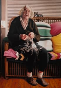 An oil painting by Josonia Palaitis depicting her elderly mother sitting on a couch with coloured knitted blankets behind her holding a messy ball of string and looking anguished