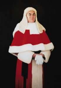 Oil painting by Josonia Palaitis depicting James Spigelman, Chief Justice of NSW standing with a pure black background holding white gloves and wearing his court wig and red and white gown