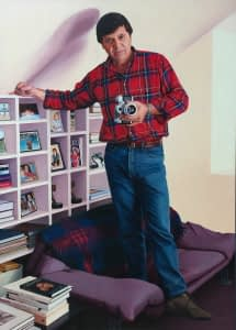 An oil painting by Josonia Palaitis depicting tv personality Ray Martin standing on a couch with a camera in his hand wearing a red an blue checked shirt with his hand resting on top of a white bookshelf with books, photos and a couple of gold tv logie awards on the shelves