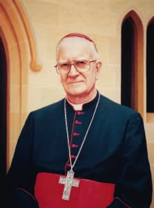 Portrait painting by Josonia Palaitis depicting Cardinal Edward Clancy dressed in his red and black robes with a crucifix on a chain around his neck standing in front of a sandstone arch