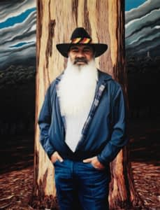 An oil painting by Josonia Palaitis depicting Patrick Dodson standing in front of a gum tree trunk wesaring jeans with his hands in his pockets and an open blue jacket that is filled by his huge white beard and he's wearing a black hat with black, red and yellow stripes in recognition of his Aboriginal ancestry