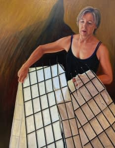 Selp portrait of Josonia Palaitis holding a broken rice paper screen wearing a black singlet with an ominous shadow in the background