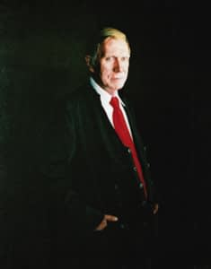 Oil painting by Josonia Palaitis depicting Justice Michael Kirby standing at turning his head to the viewer in a semi-formal pose with a red tie and a black background which envelops his suit so that it blends seamlessly and accentuates his face