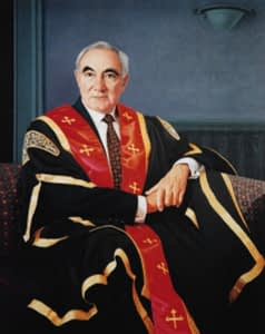 Oil painting by Josonia Palaitis depicting Professor Peter Drake sitting on a couch in a formal pose wearing his ceremonial robes in black, gold and red
