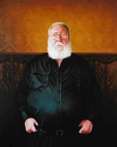 Oil on canvas portrait painting by Josonia Palaitis depicting journalist Paddy McGuiness standing and wearing a black shirt with his thumbs tucked into his belt wearing his glasses and sporting a big white beard