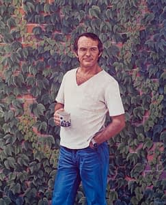 Oil painting by Josonia Palaitis depicting musician Adrian Dangerfield standing in front of a brick wall covered with vine leaves holding a mug of tea with the other hand in his pocket wearing jeans and a white t-shirt