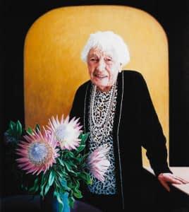 Oil painting by Josonia Palaitis depicting her aunty at the age of 100 standing in front of a yellow background wearing a black cardigan and bead necklaces with pink Australian wildflowers in the foreground