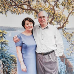 Oil painting by Josonia Palaitis depicting Prime Minister John Howard with his arm around his wife Janette Howard with Sydney Harbour and a gum tree as a backdrop from the location of Kirribilli House