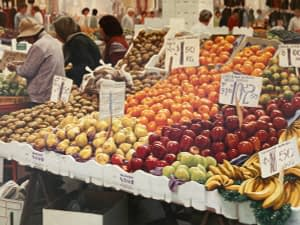 Oil Painting by Josonia Palaitis depicting a colourful fruit stall with apples, bananas, pears and mandarins with people browsing in the background